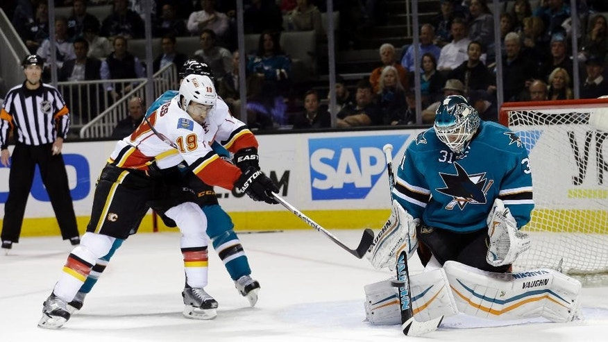 San Jose Sharks goalie Antti Niemi, right, stops a shot next to Calgary Flames' David Jones (19) during the second period of an NHL hockey game Monday, Feb. 9, 2015, in San Jose, Calif. (AP Photo/Marcio Jose Sanchez)