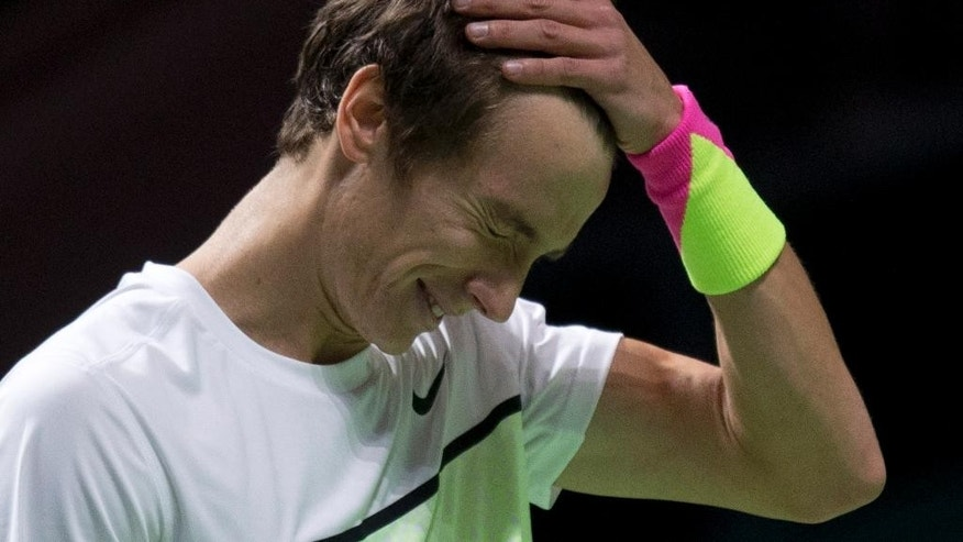 Russia's Andrey Kuznetsov grabs his head after failing to return a shot by Canada's Milos Raonic during their first round match of the 42nd ABN AMRO world tennis tournament at Ahoy Arena in Rotterdam, Netherlands, Tuesday, Feb. 10, 2015. (AP Photo/Peter Dejong)