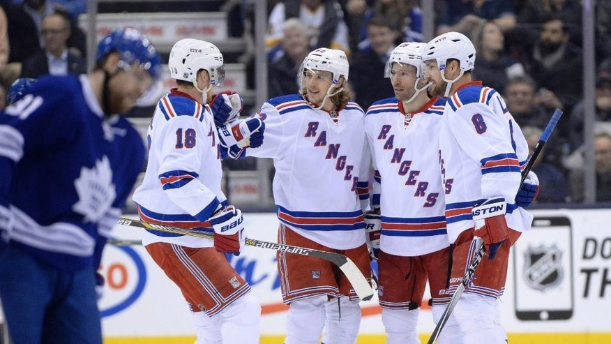 New York Rangers' Dominic Moore (28) celebrates his short-handed goal against the Toronto Maple Leafs with teammates Marc Staal (18), Carl Hagelin (62) and Kevin Klein (8) during second period NHL action in Toronto on Tuesday, Feb. 10, 2015. (AP Photo/The Canadian Press, Frank Gunn)