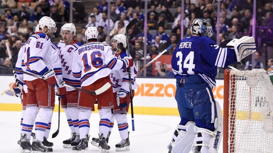 Toronto Maple Leafs goalie James Reimer, right, reacts as New York Rangers celebrate a goal by teammate Mats Zuccarello (36) during first period NHL action in Toronto on Tuesday, Feb. 10, 2015.(AP Photo/The Canadian Press, Frank Gunn)