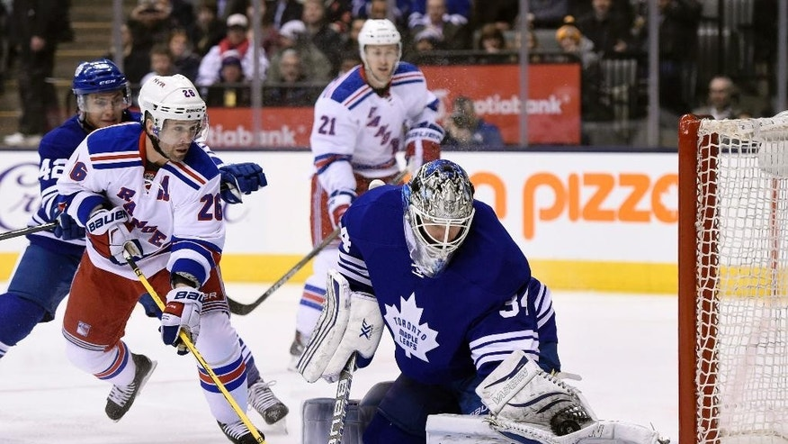 Toronto Maple Leafs goalie James Reimer, right, makes a save as New York Rangers' Martin St. Louis (26) moves in looking for a rebound during first period NHL action in Toronto on Tuesday, Feb. 10, 2015.(AP Photo/The Canadian Press, Frank Gunn)
