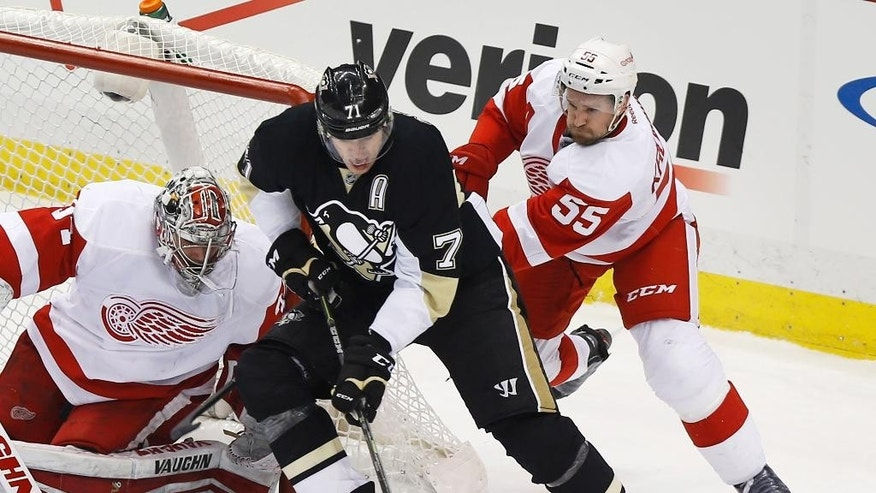 Pittsburgh Penguins' Evgeni Malkin, center, gets around Detroit Red Wings' Niklas Kronwall (55) as he maneuvers in front of Red Wings goalie Petr Mrazek during the first period of an NHL hockey game, Wednesday, Feb. 11, 2015, in Pittsburgh. (AP Photo/Keith Srakocic)