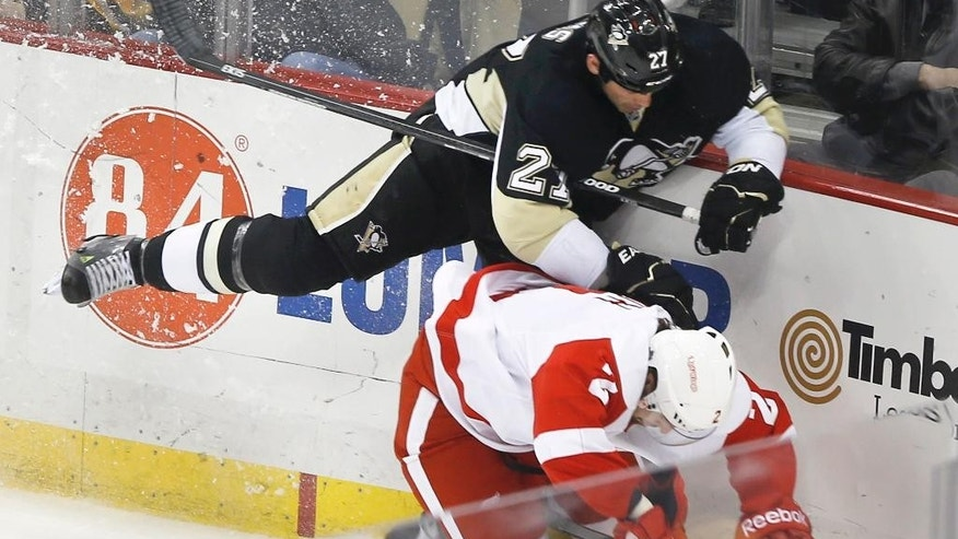 Pittsburgh Penguins' Craig Adams (27) checks Detroit Red Wings' Brendan Smith along the boards during the first period of an NHL hockey game, Wednesday, Feb. 11, 2015, in Pittsburgh. (AP Photo/Keith Srakocic)