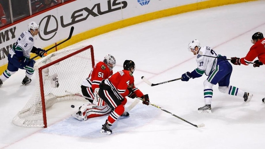 Vancouver Canucks left wing Daniel Sedin (22) scores the winning goal past Chicago Blackhawks goalie Corey Crawford (50) as Luca Sbisa (5), Niklas Hjalmarsson, and Marian Hossa watch during an overtime period of an NHL hockey game Wednesday, Feb. 11, 2015, in Chicago. The canucks won 5-4. (AP Photo/Charles Rex Arbogast)