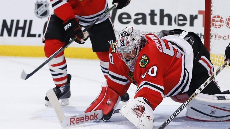 Chicago Blackhawks goalie Corey Crawford (50) dives on a loose puck during the first period of an NHL hockey game against the Vancouver Canucks Wednesday, Feb. 11, 2015, in Chicago. (AP Photo/Charles Rex Arbogast)