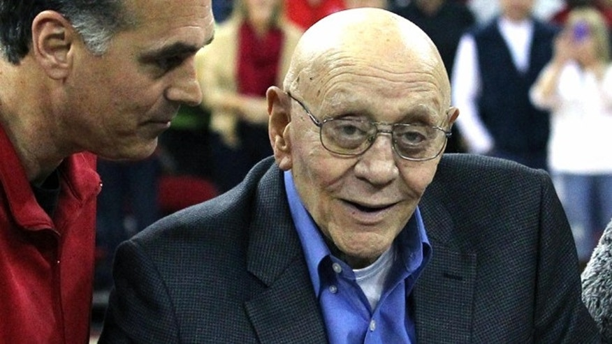 In this March 1, 2014, file photo, Jerry Tarkanian is escorted by his son, Danny, during halftime ceremonies honoring the former basketball coach at Fresno State University in Fresno, Calif.