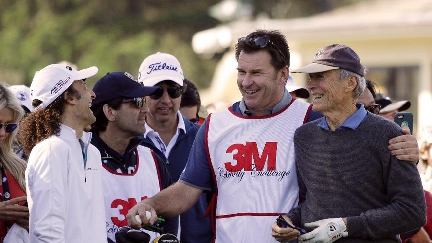 Musician Kenny G, left, laughs as actor Clint Eastwood, right, is embraced by his caddie Nick Faldo, second from right, on the first tee of the Pebble Beach Golf Links during the celebrity challenge event of the AT&T Pebble Beach National Pro-Am golf tournament Wednesday, Feb. 11, 2015, in Pebble Beach, Calif. (AP Photo/Eric Risberg)
