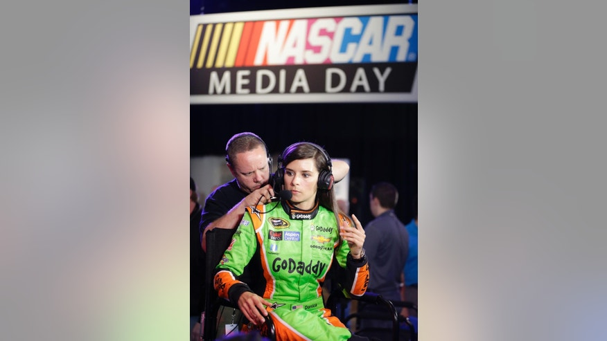 A technician adjusts the headset for driver Danica Patrick as she prepares for an interview during NASCAR media day at Daytona International Speedway, Thursday, Feb. 12, 2015, in Daytona Beach, Fla. (AP Photo/John Raoux)