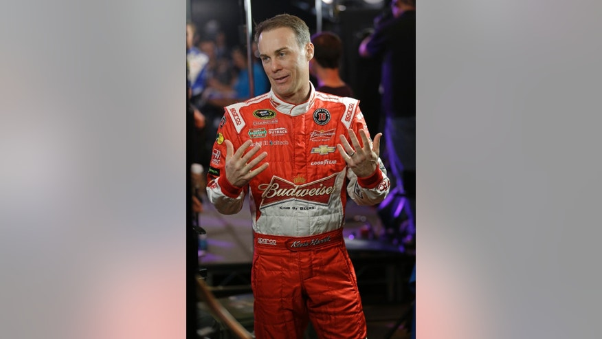Kevin Harvick talks with members of a broadcast crew after finishing a television interview during NASCAR media day at Daytona International Speedway, Thursday, Feb. 12, 2015, in Daytona Beach, Fla. (AP Photo/John Raoux)