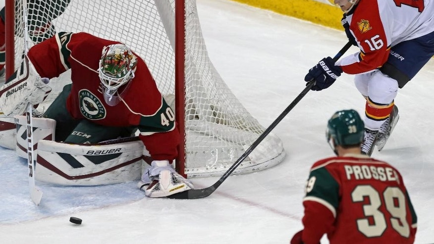 Minnesota Wild goalie Devan Dubnyk, left, stops a scoring attempt by Florida Panthers' Aleksander Barkov, right, of Finland, in the first period of an NHL hockey game, Thursday, Feb. 12, 2015, in St. Paul, Minn. (AP Photo/Jim Mone)