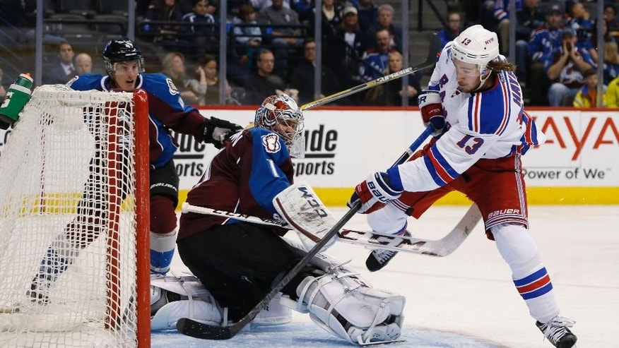New York Rangers right wing Kevin Hayes, right, scores a goal against Colorado Avalanche goalie Semyon Varlamov, of Russia, left, as defenseman Tyson Barrie, back, looks on in the second period of an NHL hockey game Thursday, Feb. 12, 2015, in Denver. (AP Photo/David Zalubowski)