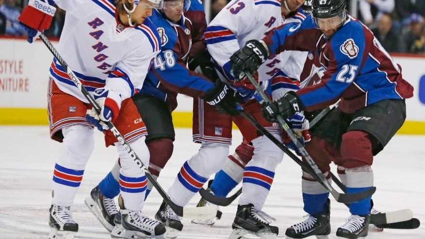 From left, New York Rangers left wing Carl Hagelin, of Sweden, battles for control of the puck with Colorado Avalanche center Daniel Briere, Rangers right wing Kevin Hayes and Avalanche center Maxime Talbot in the first period of an NHL hockey game Thursday, Feb. 12, 2015, in Denver. (AP Photo/David Zalubowski)