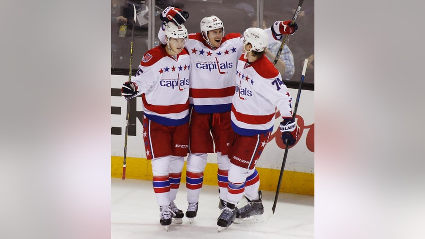 Washington Capitals' Jay Beagle, center, celebrates with teammates Andre Burakovsky, left, and John Carlson after scoring a goal against the San Jose Sharks during the first period of an NHL hockey game Wednesday, Feb. 11, 2015, in San Jose, Calif. (AP Photo/George Nikitin)