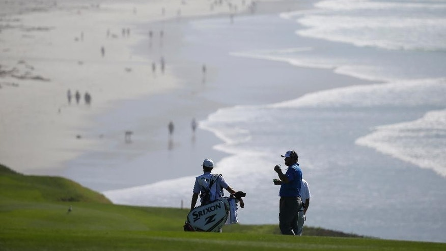 J.B. Holmes waits to hit his approach shot from the ninth fairway of the Pebble Beach Golf Links as his caddie, Brandon Parsons, left, looks on during the first round of the AT&T Pebble Beach National Pro-Am golf tournament Thursday, Feb. 12, 2015, in Pebble Beach, Calif. (AP Photo/Eric Risberg)