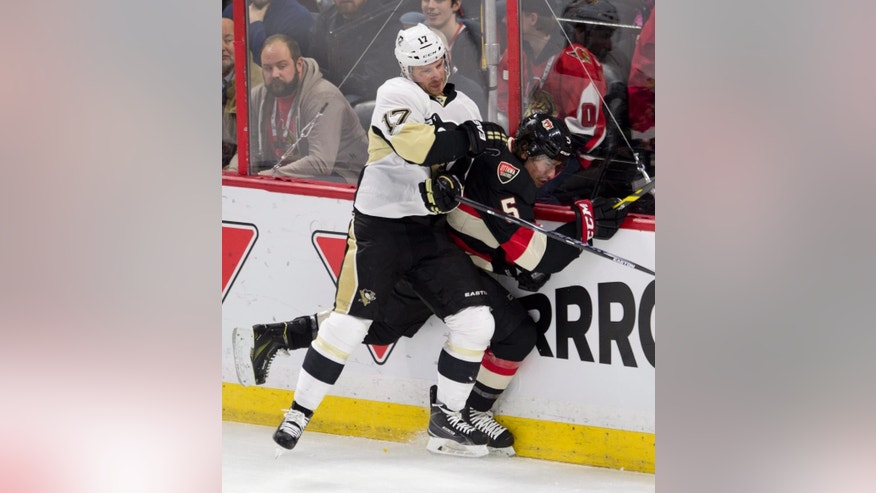 Pittsburgh Penguins left wing Blake Comeau sends Ottawa Senators defenseman Cody Ceci into the boards during the first period on an NHL hockey game, Thursday, Feb. 12, 2015 in Ottawa, Ontario.  (AP Photo/Canadian Press, Adrian Wyld)