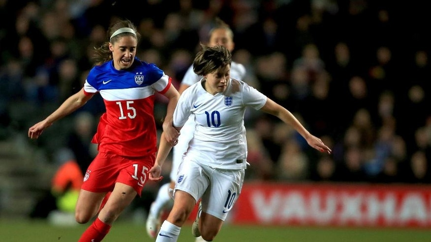 England's Fran Kirby, centre battles to hold off a challenge from Morgan Brian of the US, during the international friendly match between England and the US,  at the Stadium:mk, in Milton Keynes, England, Friday Feb. 13, 2015. (AP Photo/PA, Nick Potts) UNITED KINGDOM OUT
