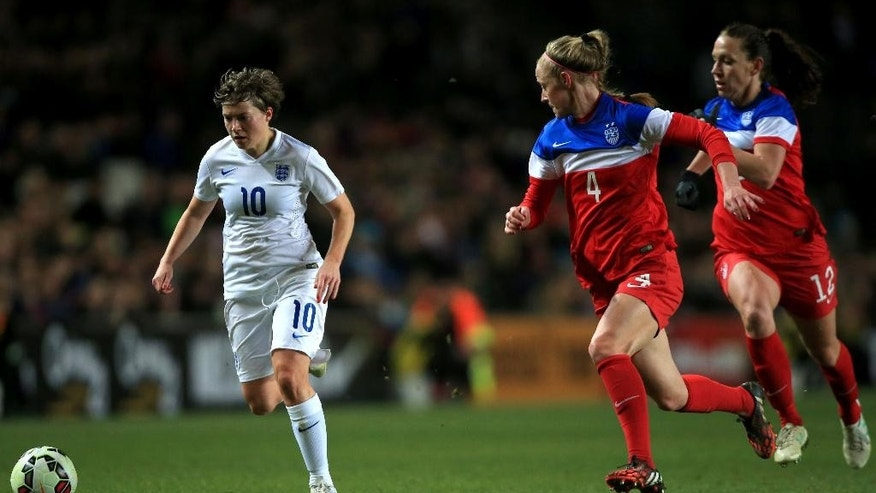 England's Fran Kirby, left battles to hold off a  challenge from Becky Sauerbrunn , centre and Lauren Holiday, of the US,  during the international friendlysoccer match between England and the US,  at the Stadium:mk, in Milton Keynes, England, Friday Feb. 13, 2015. (AP Photo/PA, Nick Potts) UNITED KINGDOM OUT
