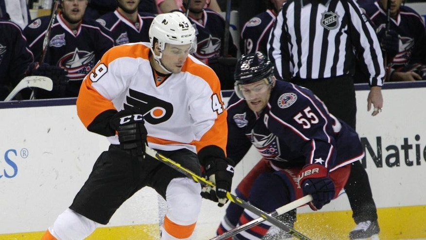 Philadelphia Flyers' Scott Laughton, left, tries to clear the puck past Columbus Blue Jackets' Mark Letestu during the first period of an NHL hockey game Friday, Feb. 13, 2015, in Columbus, Ohio. (AP Photo/Jay LaPrete)