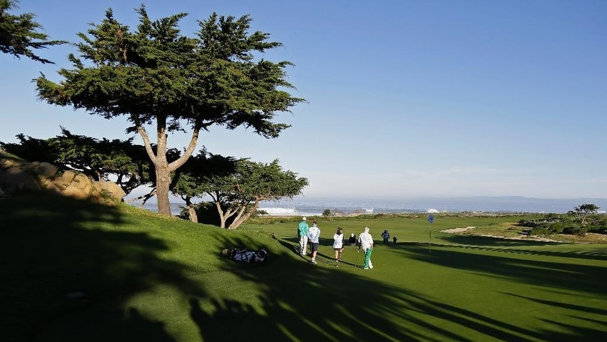 Shadows fall on the 10th green of the Monterey Peninsula Country Club Shore Course as the group of John Daly and Tommy Gainey wait to putt during the second round of the AT&T Pebble Beach National Pro-Am golf tournament Friday, Feb. 13, 2015, in Pebble Beach, Calif. (AP Photo/Eric Risberg)