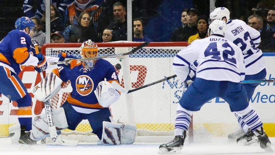 RETRANSMISSION TO CORRECT WHO SCORED THE GOAL - New York Islanders goalie Jaroslav Halak (41) of Slovakia watches the puck as a shot scored by Toronto Maple Leafs Trevor Smith (23) flies in front of him with New York Islanders defenseman Nick Leddy (2) defending in the second period of an NHL hockey game at Nassau Coliseum in Uniondale, N.Y., Thursday, Feb. 12, 2015. Toronto Maple Leafs center Tyler Bozak (42) and Toronto Maple Leafs center Trevor Smith (23) look on, right. (AP Photo/Kathy Willens)