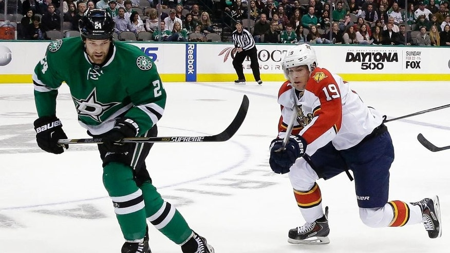 Florida Panthers right wing Scottie Upshall (19) and Dallas Stars defenseman Jordie Benn (24) skate for the puck during the first period of an NHL hockey game Friday, Feb. 13, 2015, in Dallas. (AP Photo/LM Otero)