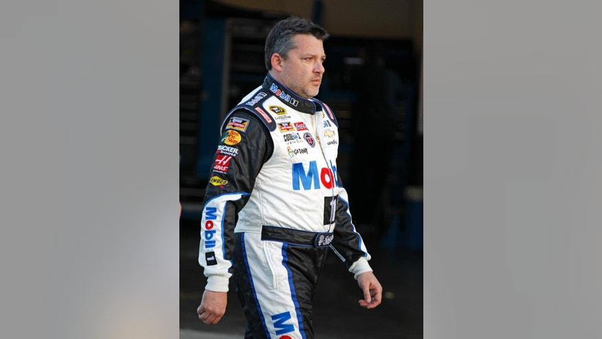 Tony Stewart walks to the garages after there was an issue with the weight of his car during a practice session for rhw NASCAR Sprint Cup Series auto race at Daytona International Speedway, Friday, Feb. 13, 2015, in Daytona Beach, Fla. (AP Photo/Terry Renna)