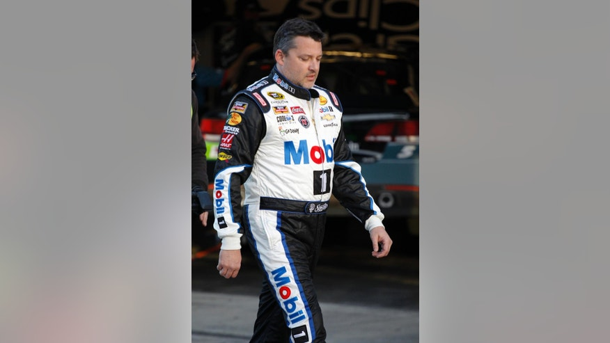 Tony Stewart walks to the garages after there was an issue with the weight of his car during a practice session for the NASCAR Sprint Cup Series auto race at Daytona International Speedway, Friday, Feb. 13, 2015, in Daytona Beach, Fla. (AP Photo/Terry Renna)