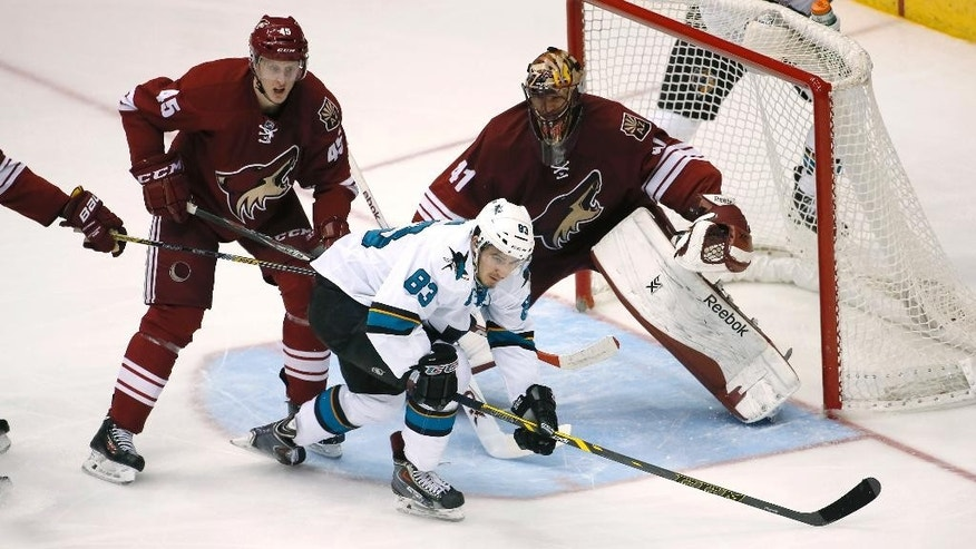 San Jose Sharks' Matt Nieto (83) reaches for the puck as Arizona Coyotes' Andrew Campbell (45) and goalie Mike Smith defend during the second period of an NHL hockey game, Friday, Feb. 13, 2015, in Glendale, Ariz. (AP Photo/Matt York)
