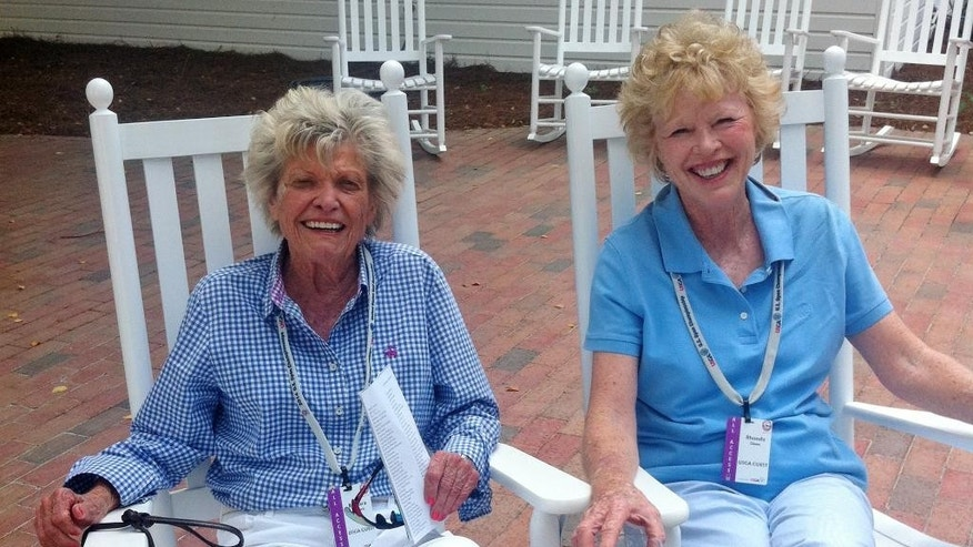 In this photo taken June 17, 2014, Rhonda Glenn, right, sits on the patio at Pinehurst Resort in Pinehurst, N.C., with longtime friend and former U.S. women's amateur champion Barbara Romack. Glenn, the first female anchor on SportsCenter and later a USGA historian and author, died Thursday night, Feb. 12, 2015, after a long illness said Romack. She was 68. (AP Photo/Doug Fergson)
