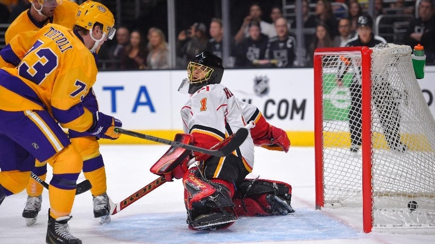Los Angeles Kings center Tyler Toffoli, front left, scores on Calgary Flames goalie Jonas Hiller, of Switzerland, during the second period of an NHL hockey game, Thursday, Feb. 12, 2015, in Los Angeles. (AP Photo/Mark J. Terrill)