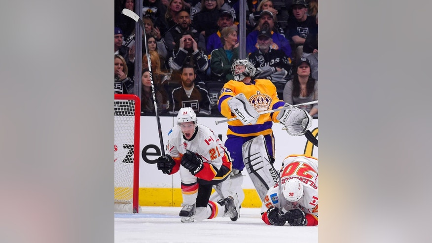 Calgary Flames left wing Mason Raymond, left, celebrates his goal as Los Angeles Kings goalie Jonathan Quick, center, watches and left wing Curtis Glencross falls during the second period of an NHL hockey game, Thursday, Feb. 12, 2015, in Los Angeles. (AP Photo/Mark J. Terrill)