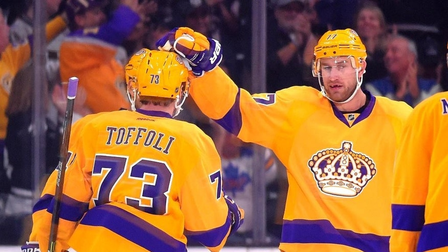 Los Angeles Kings center Tyler Toffoli, left, is congratulated by center Jeff Carter during the first period of an NHL hockey game against the Calgary Flames, Thursday, Feb. 12, 2015, in Los Angeles. (AP Photo/Mark J. Terrill)