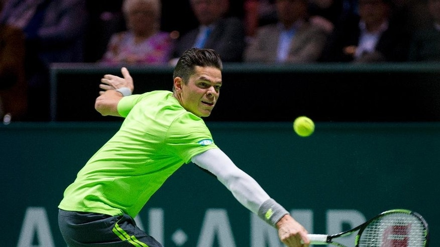 Milos Raonic of Canada returns the ball to Stan Wawrinka of Switzerland during their semifinal match of the 42nd ABN AMRO world tennis tournament at Ahoy Arena in Rotterdam, Netherlands, Saturday, Feb. 14, 2015. (AP Photo/Patrick Post)