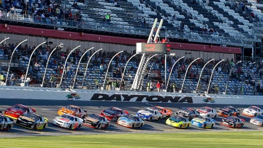 Cars speed past the starting line led Mark Thompson, far left bottom, and Cody Coughlin, far left top, to begin the ARCA series auto race at Daytona International Speedway, Saturday, Feb. 14, 2015, in Daytona Beach, Fla. (AP Photo/Terry Renna)