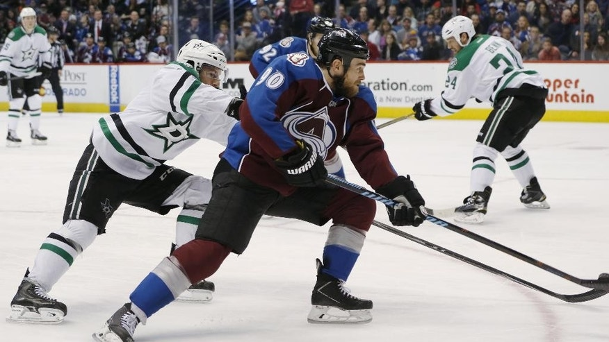Colorado Avalanche center Ryan O'Reilly, right, takes a shot on goal as Dallas Stars defenseman Jason Demers defends in the second period of an NHL hockey game Saturday, Feb. 14, 2015, in Denver. (AP Photo/David Zalubowski)