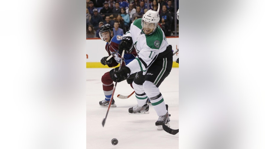 Dallas Stars left wing Curtis McKenzie, front, clears the puck from in fornt of the net as Colorado Avalanche left wing Alex Tanguay covers in the second period of an NHL hockey game Saturday, Feb. 14, 2015, in Denver. (AP Photo/David Zalubowski)