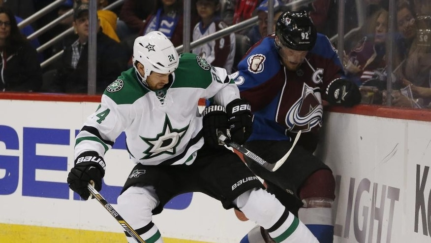 Dallas Stars defenseman Jordie Benn, left, uses his skate to push the puck away from Colorado Avalanche left wing Gabriel Landeskog, of Sweden, in the second period of an NHL hockey game Saturday, Feb. 14, 2015, in Denver. (AP Photo/David Zalubowski)