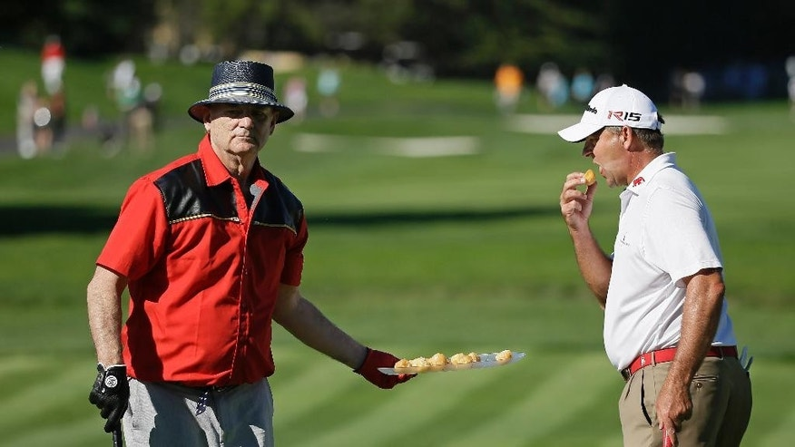 Actor Bill Murray, left, serves a tray of donut holes to Dicky Pride, right, on the second green of the Pebble Beach Golf Links during the third round of the AT&T Pebble Beach National Pro-Am golf tournament Saturday, Feb. 14, 2015, in Pebble Beach, Calif. Murray took the whole tray from a woman who offered him one and then gave them out to other fans and players on the green. (AP Photo/Eric Risberg)
