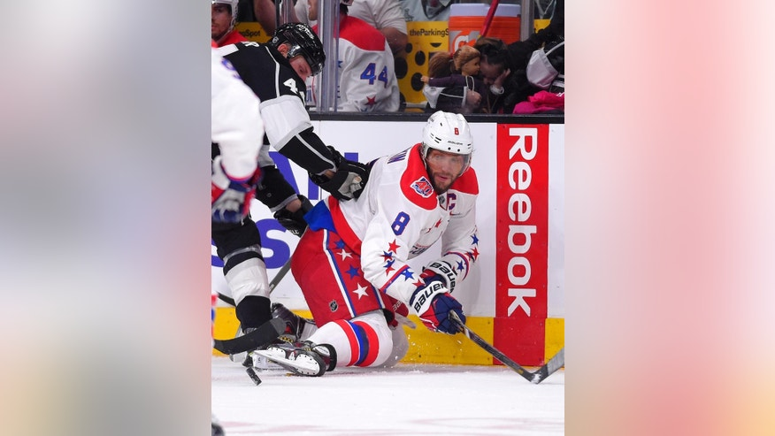 Washington Capitals left wing Alex Ovechkin, right, of Russia, passes the puck under pressure from Los Angeles Kings defenseman Robyn Regehr, of Brazil, during the second period of an NHL hockey game, Saturday, Feb. 14, 2015, in Los Angeles. (AP Photo/Mark J. Terrill)