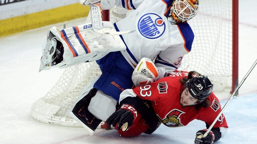 Ottawa Senators' Mika Zibanejad, right, slams into Edmonton Oilers goalie Viktor Fasth during the first period of their NHL hockey game in Ottawa on Saturday, Feb. 14, 2015. (AP Photo/The Canadian Press, Sean Kilpatrick)