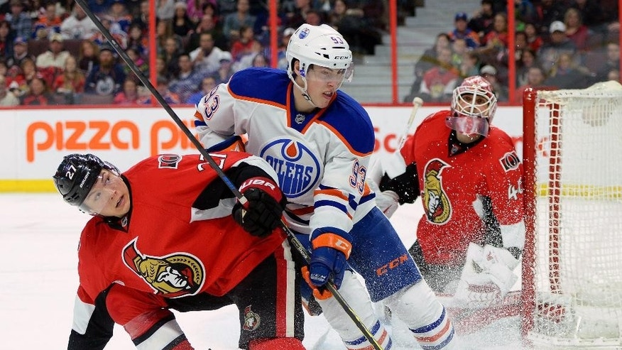 Ottawa Senators' Curtis Lazar, left, fights to keep Edmonton Oilers' Ryan Nugent-Hopkins, center, from the puck as Senators goalie Robin Lehner looks on during the third period of their NHL hockey game in Ottawa on Saturday, Feb. 14, 2015. The Senators defeated the Oilers 7-2. (AP Photo/The Canadian Press, Sean Kilpatrick)