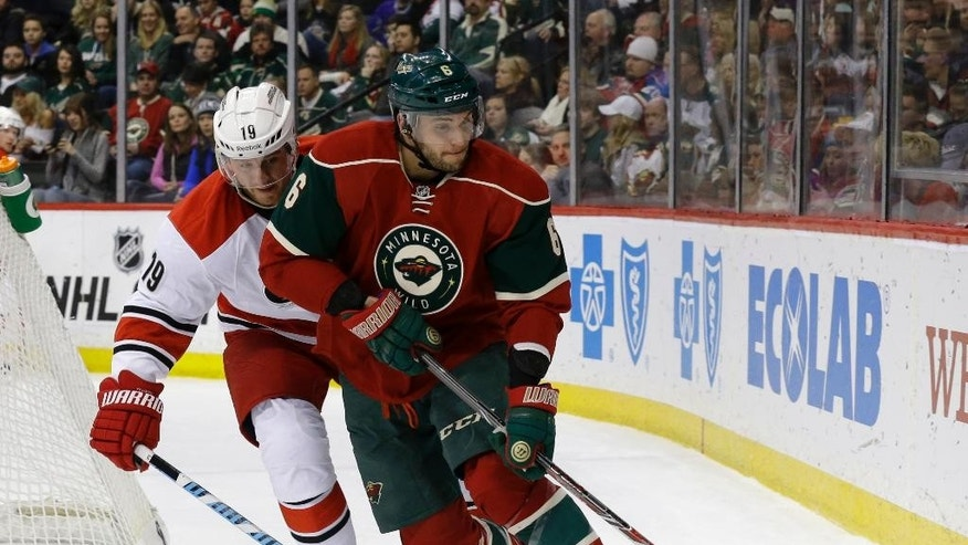Minnesota Wild defenseman Marco Scandella (6) controls the puck in front of Carolina Hurricanes left wing Jiri Tlusty (19), of the Czech Republic, during the second period of an NHL hockey game in St. Paul, Minn., Saturday, Feb. 14, 2015. (AP Photo/Ann Heisenfelt)