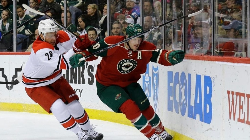 Minnesota Wild defenseman Ryan Suter (20) and Carolina Hurricanes right wing Alexander Semin (28), of Russia, chase the puck during the second period of an NHL hockey game in St. Paul, Minn., Saturday, Feb. 14, 2015. (AP Photo/Ann Heisenfelt)