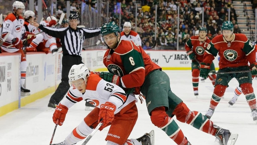 Carolina Hurricanes left wing Jeff Skinner (53) and Minnesota Wild defenseman Marco Scandella (6) battle for the puck during the second period of an NHL hockey game in St. Paul, Minn., Saturday, Feb. 14, 2015. (AP Photo/Ann Heisenfelt)