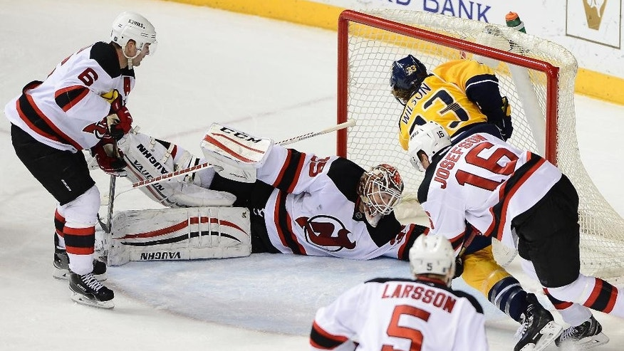 Nashville Predators center Colin Wilson, top right, scores the go-ahead goal against New Jersey Devils goalie Cory Schneider (35) in the third period of an NHL hockey game, Saturday, Feb. 14, 2015, in Nashville, Tenn. Also defending are Devils' Andy Greene (6) and Jacob Josefson (16), of Sweden. The Predators won 3-1. (AP Photo/Mark Zaleski)