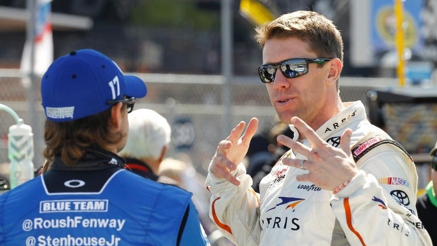Carl Edwards, right, talks with Ricky Stenhouse Jr. before qualifying for the Daytona 500 NASCAR Sprint Cup Series auto race at Daytona International Speedway, Sunday, Feb. 15, 2015, in Daytona Beach, Fla. (AP Photo/Terry Renna)