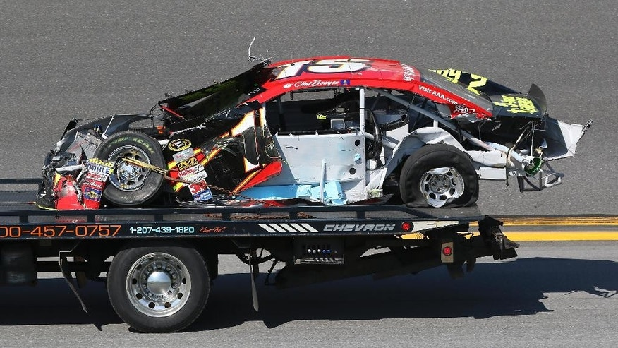 Clint Bowyer's car is taken back to the garage after he was involved in a wreck during qualifying for the Daytona 500 NASCAR Sprint Cup Series auto race at Daytona International Speedway, Sunday, Feb. 15, 2015, in Daytona Beach, Fla. (AP Photo/Reinhold Matay)
