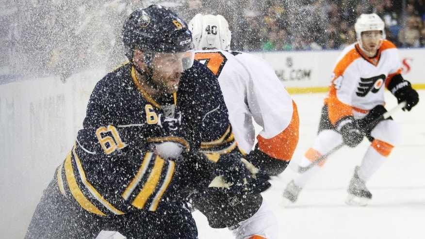 Buffalo Sabres' Andre Benoit (61) battles along the boards against Philadelphia Flyers' Vincent Lecavalier, back, during the first period of an NHL hockey game, Sunday, Feb. 15, 2015, in Buffalo, N.Y. (AP Photo/Jen Fuller)