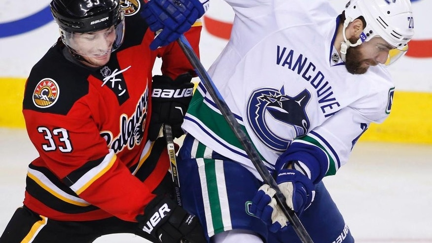 Vancouver Canucks' Chris Higgins, right, battles with Calgary Flames' Raphael Diaz during the second period of an NHL hockey game Saturday, Feb. 14, 2015, in Calgary, Alberta. (AP Photo/The Canadian Press, Larry MacDougal)