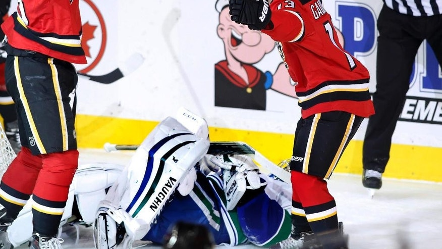 Calgary Flames' Sean Monahan, left, celebrates his goal with Johnny Gaudreau, right, as Vancouver Canucks' Ryan Miller lies on the ice during the second period of an NHL hockey game Saturday, Feb. 14, 2015, in Calgary, Alberta. (AP Photo/The Canadian Press, Larry MacDougal)
